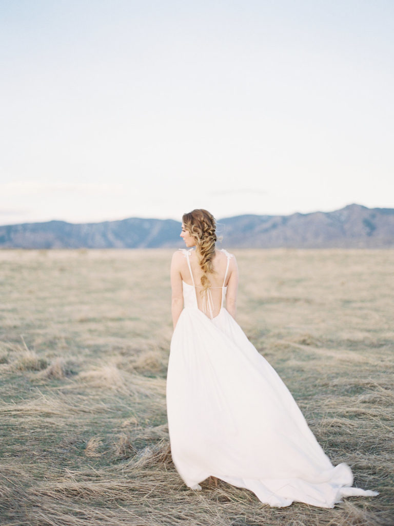 Colorado Romantic Spring Elopement bride standing with her wedding dress blowing in the wind