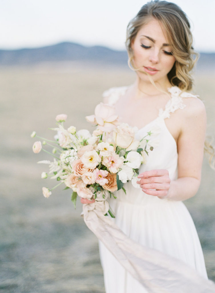 Colorado Romantic Spring Elopement bride looking down at her bouquet created by flora by nora