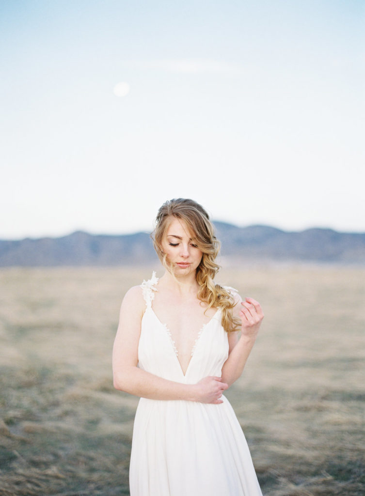 bride wearing a wedding dress looking down with the moon behind her in our Colorado Romantic Spring Elopement