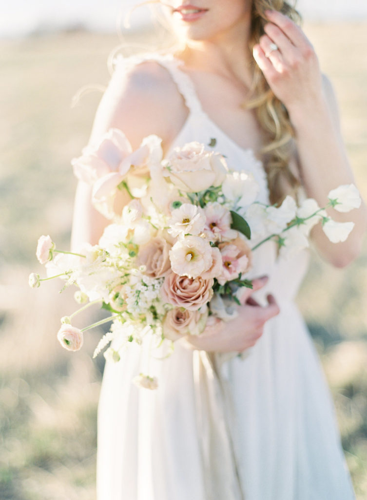 Colorado Romantic Spring Elopement bride holding a bouquet by flora by nora with the sunshine behind her