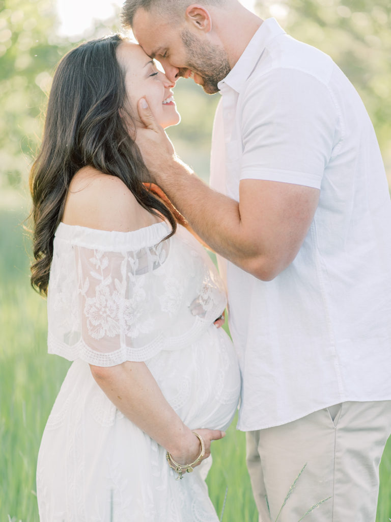expecting parents forehead to forehead during their Littleton maternity session