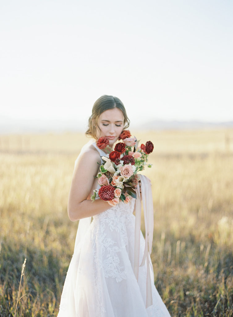 Bride holding a beautiful bouquet made by Helios Floral during a Romantic Al Fresco Wedding Inspiration at Stonewall Farm