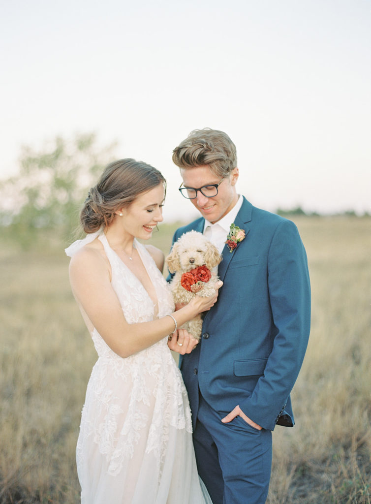 Bride and groom holding a dog photographed by Decorus photography during a Romantic Al Fresco Wedding Inspiration at Stonewall Farm