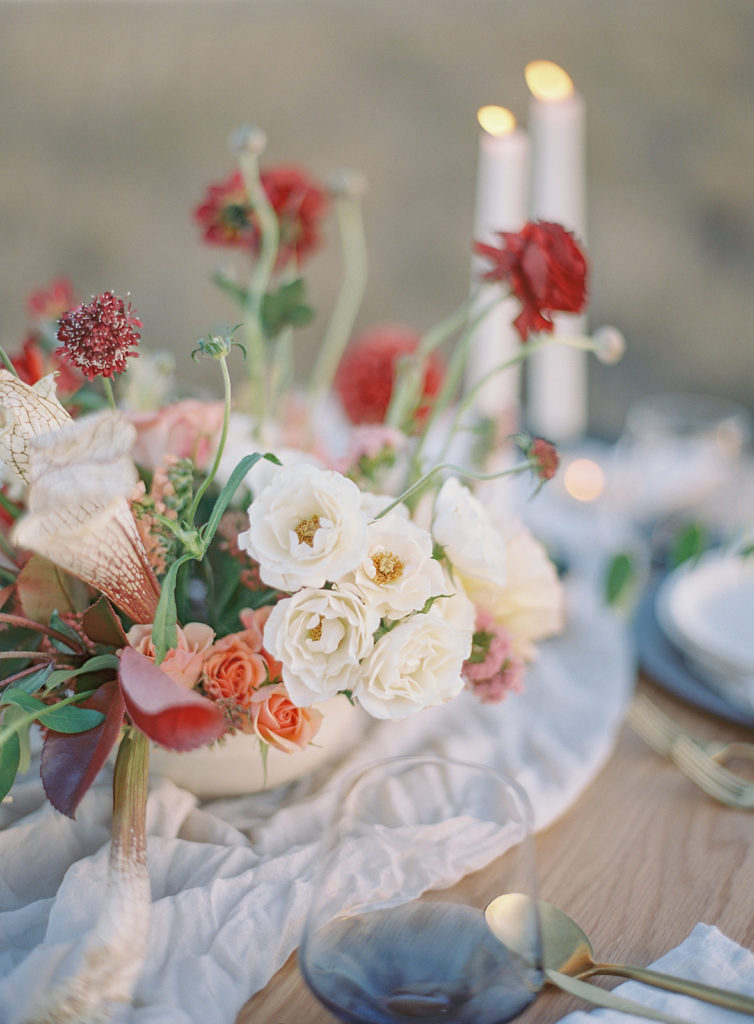 Close up of a table centerpiece designed by Helios Floral photographed by Decorus photography during a Romantic Al Fresco Wedding Inspiration at Stonewall Farm